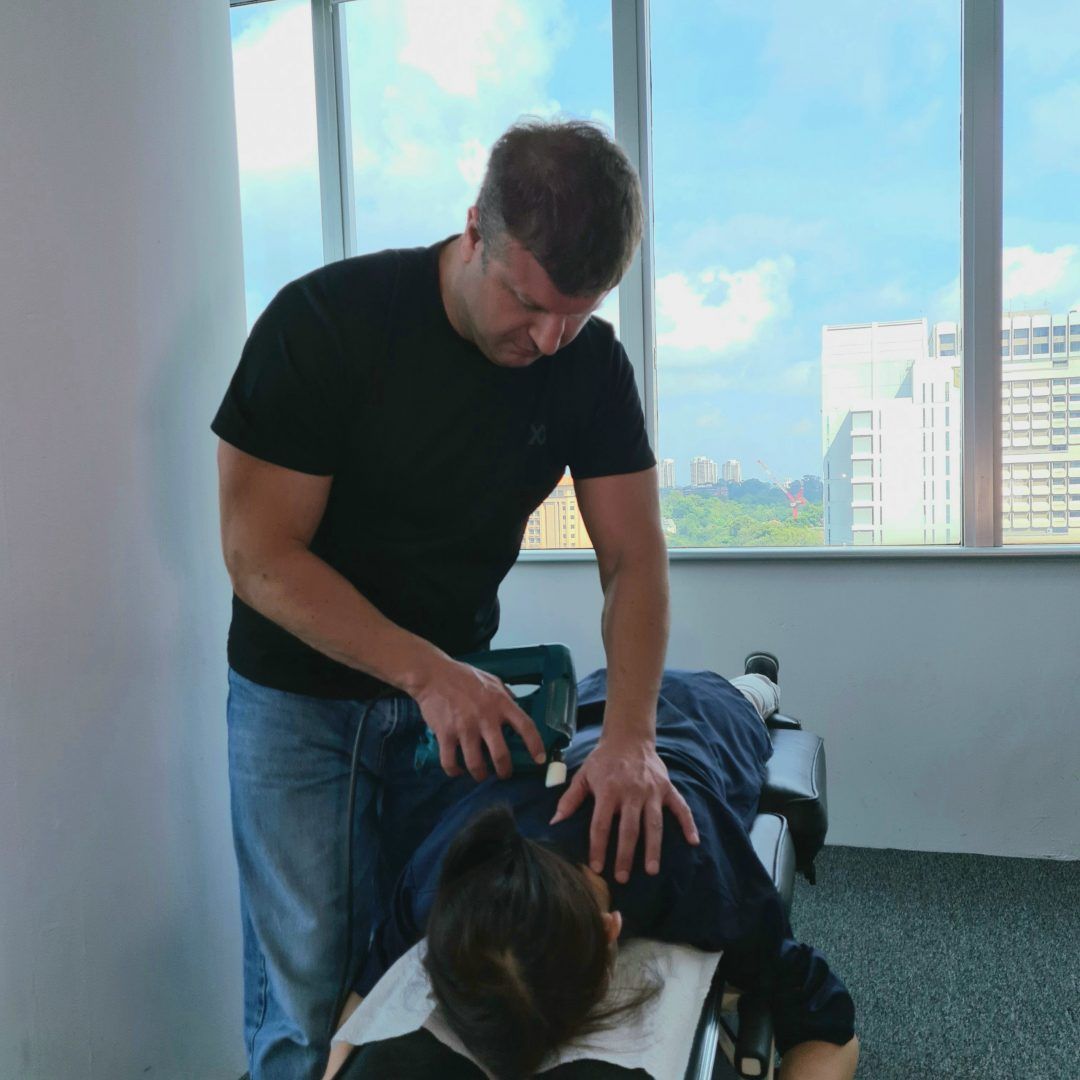 Chiropractor singapore percussion massage forneck pain